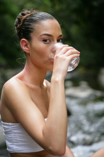 Woman drinking water by a brook
