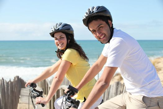 young couple riding near seafront
