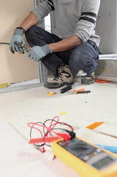 Electrician kneeling by voltmeter