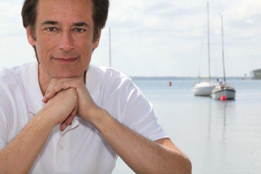 Man smiling by boating lake