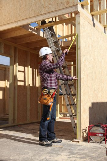 Contractor inspecting woodwork on house under construction