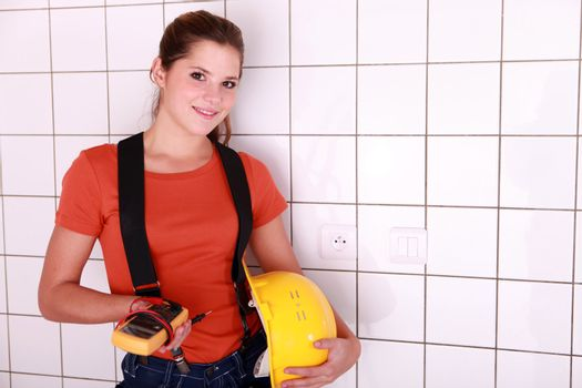 handywoman posing with an ammeter and a helmet