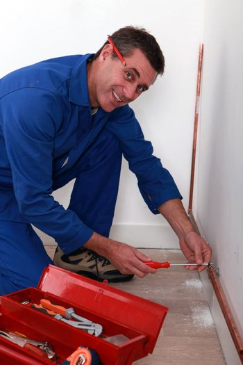 Plumber fastening copper pipe to wall