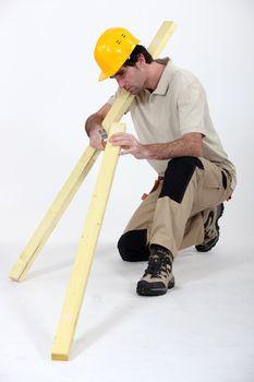 carpenter with lumber at work