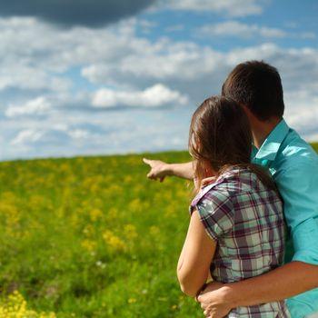 lovers look around on yellow flower field
