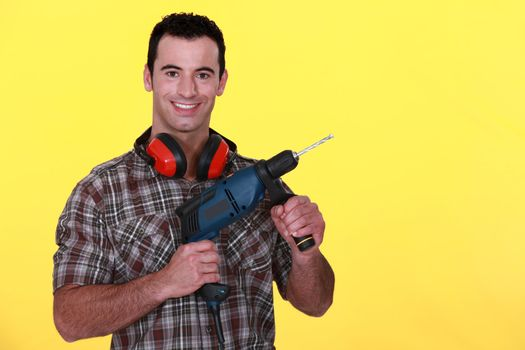 Man with power drill and earmuffs