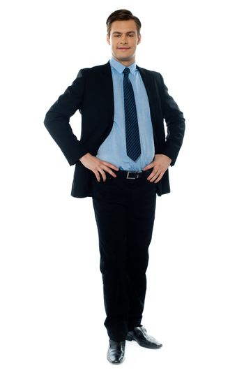 Full length view of a young businessperson posing with hands on his waist
