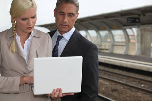 Business couple with a laptop on a railway platform
