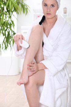 Woman using epilator in bathroom
