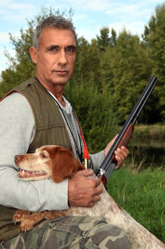 Hunter with a shotgun and spaniel
