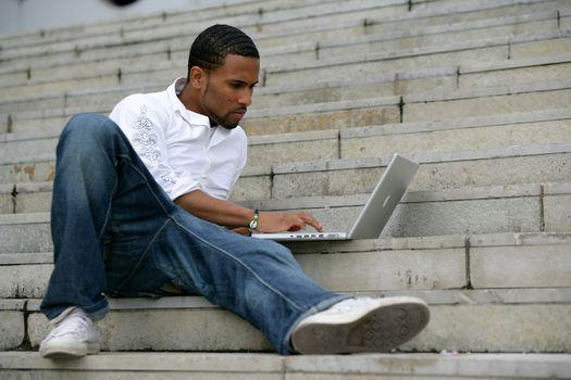 black man working on laptop in stairs