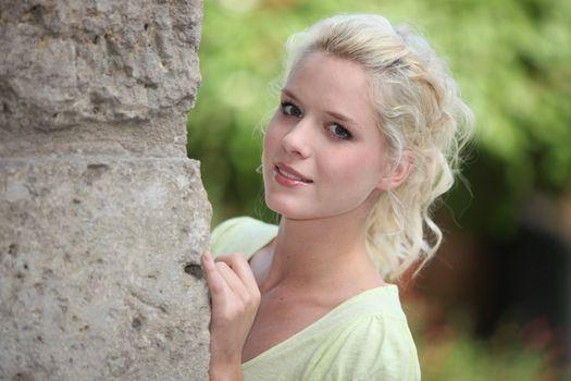 Girl hiding behind a stonewall
