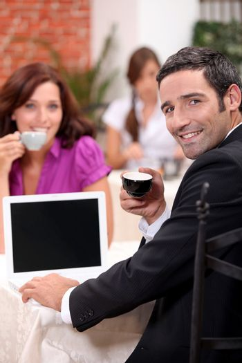 Couple drinking expresso in a cafe with a laptop screen left blank for your image