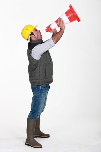 full-length picture of builder in profile shouting in construction cone