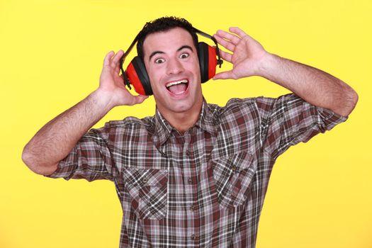 happy man wearing earmuffs cancelling noise