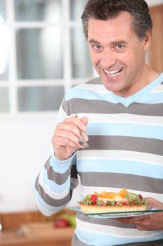 Smiling man eating a fruit flan