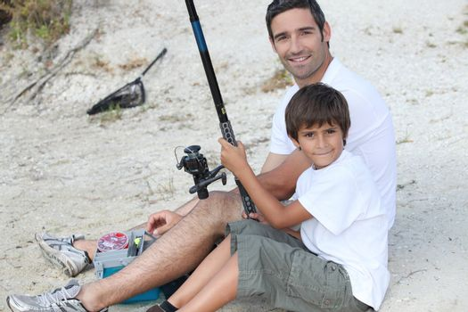 father and son fishing at riverbank