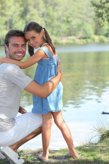 Father and daughter standing on a riverbank