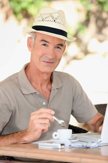Older man outside with a laptop and an expresso