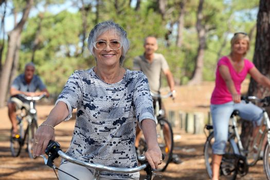 a 65 years old woman in first plan and three other people doing bike in the forest