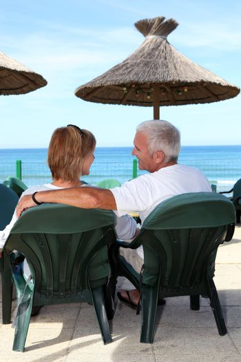Middle-aged couple sat by the seafront