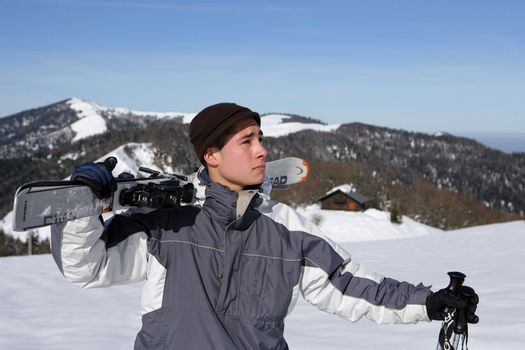 Boy with skis on shoulder