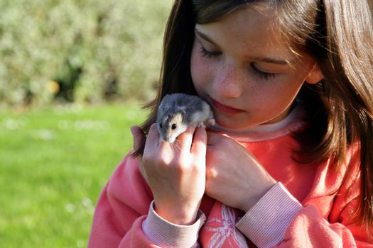 Young girl holding a rodent