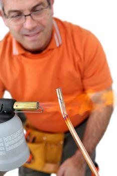 Plumber soldering pipe