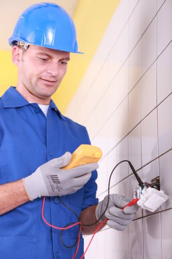 electrician is checking an outlet with an ammeter