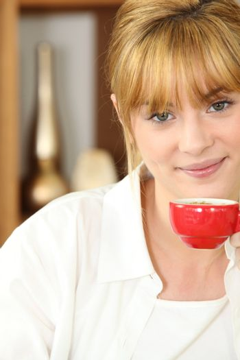 Young woman drinking a cup of expresso coffee