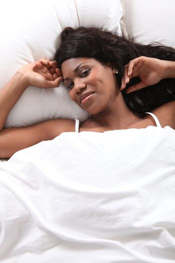 black woman waking up in her bed