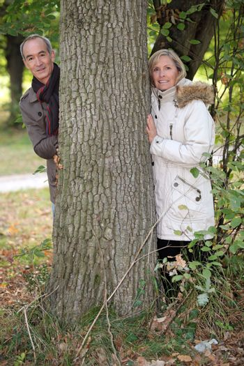 Couple standing behind a tree trunk