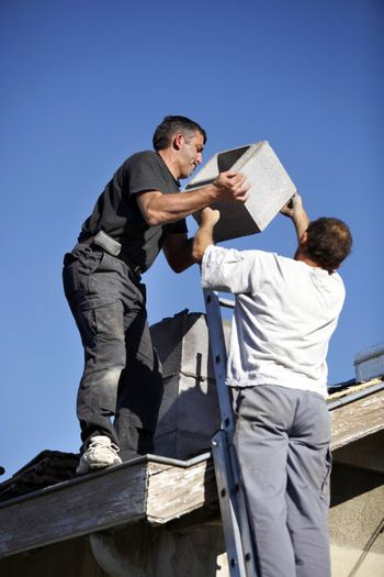 Roofers installing chimney
