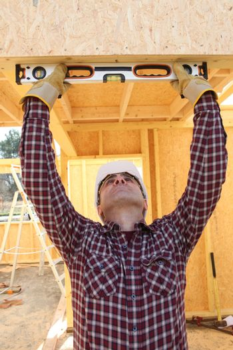Man using spirit level to check woodwork