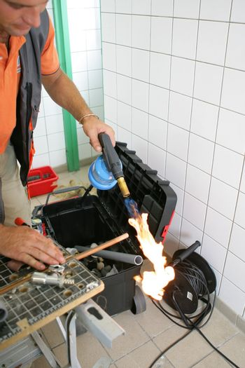 Plumber heating up copper pipe