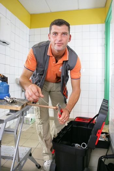 Artisan cutting copper piping