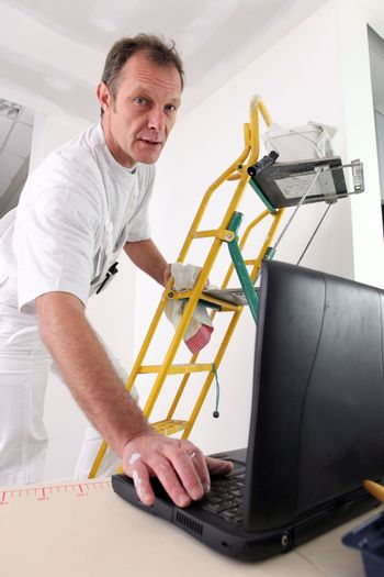 Painter checking instructions on the Internet
