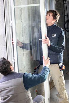 Laborers installing window