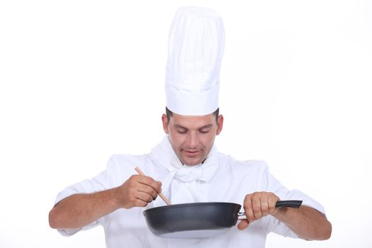 Chef stirring contents of saucepan