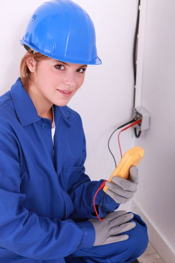 dow-eyed female electrician at work with tester