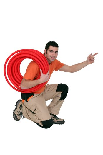 Plumber with coiled pipe pointing in to the distance