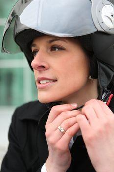 Woman fastening a motorcycle helmet
