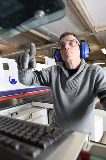 Man using computer controlled factory machine