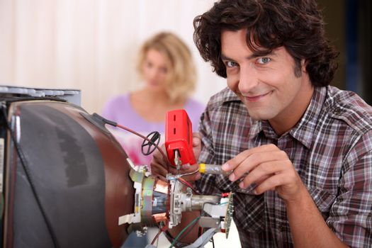 Man repairing television set