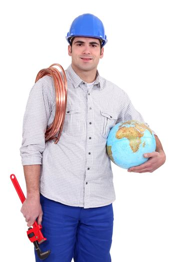 Tradesman holding a globe, a coiled copper wire and a pipe wrench