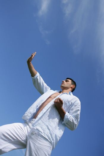 Man practicing judo against a blue sky