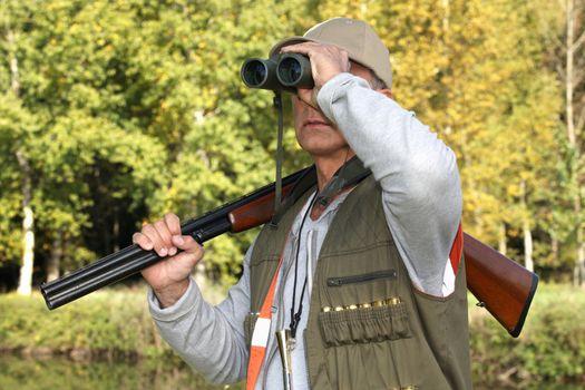 hunter with rifle looking through binoculars