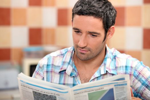 Man reading a journal in the kitchen