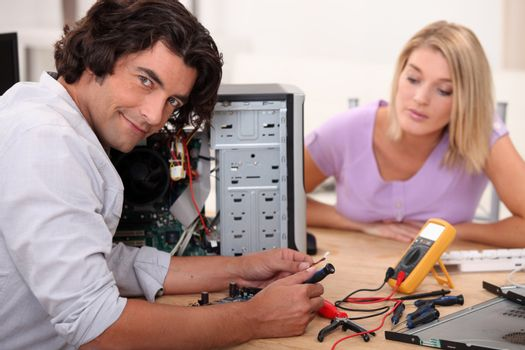 mid long hair man is repairing a computer in front of a blonde woman