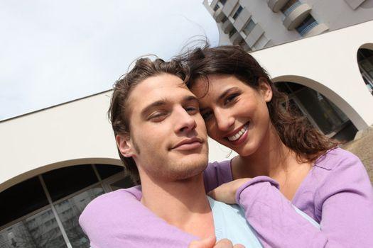 Smiling couple outside a block of flats